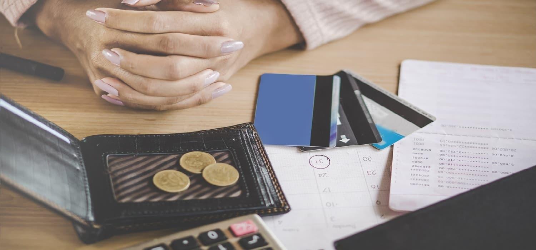 кредитна календар з датою платежу за онлайн кредит, карта, гаманець з копіками на столі поряд з руками чоловіка