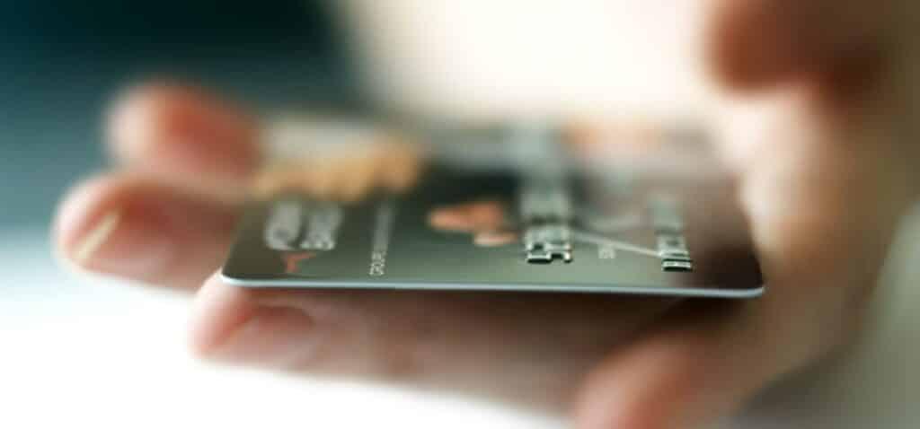 банківська кредитна карта золотистого кольору в руці людини