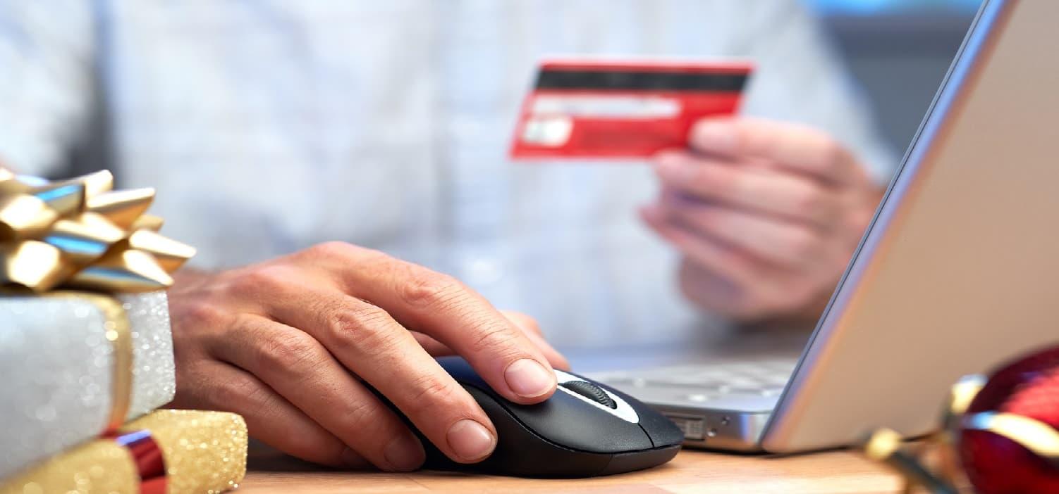 ноутбук та червона кредитка в руках чоловіка, який хоче взяти кредит онлайн