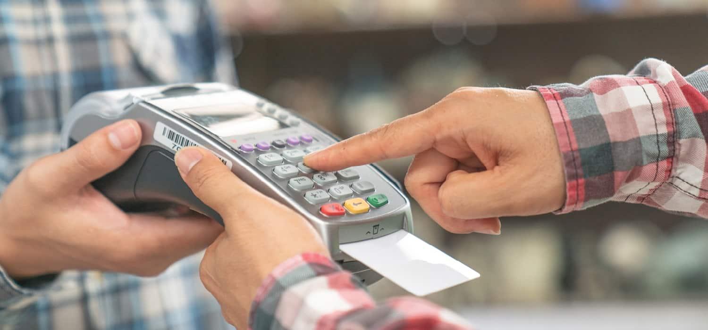 платіжна картка та термінал для оплати на касі