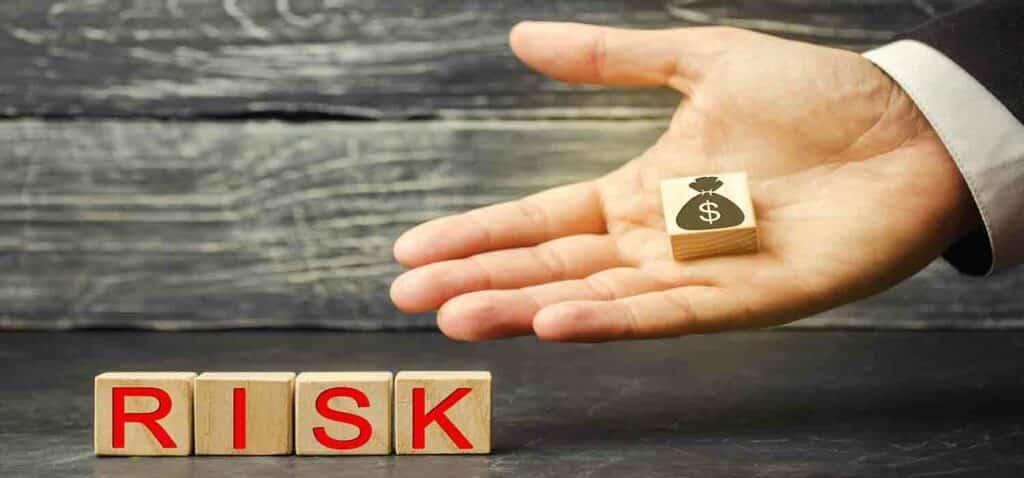 Гроші в руках інвестора, який вкладає їх в інвестиційний проект, та напис ризик