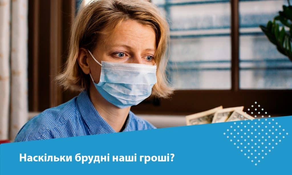 жінка в масці тримає гроші в руках