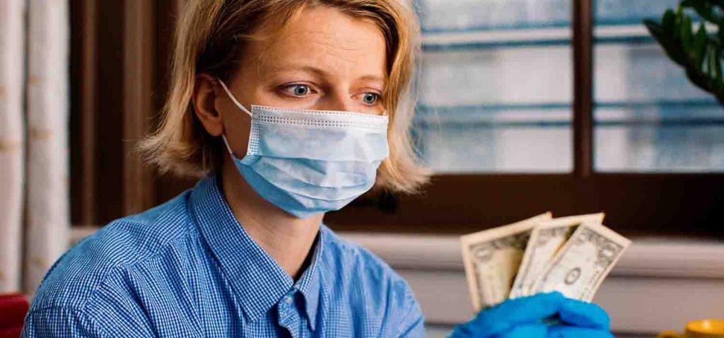 Жінка в масці тримає гроші