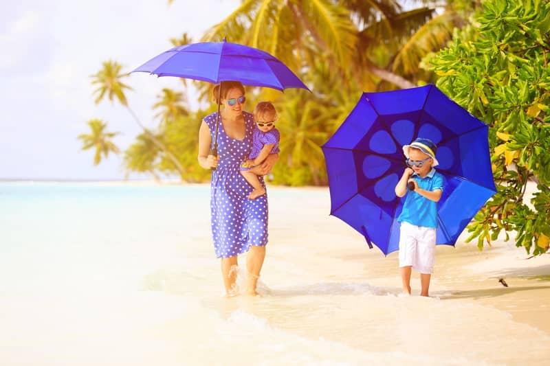семейство на плажа с чадъри срещу слънцето - застраховане