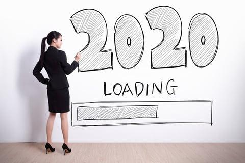 Wanita karir menulis tahun baru 2020 sebagai resolusi kebebasan finansial dengan latar belakang dinding putih